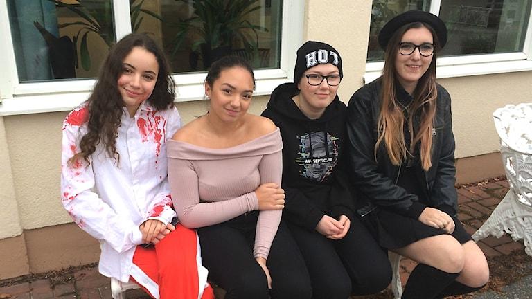 Fyra gymnasietjejer sitter på en bänk