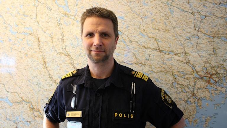 Kenneth Bergquist står i sin uniform framför en karta.