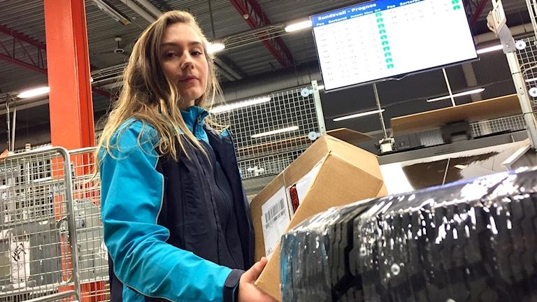 Daniella Boija som sorterar paket hos Postnord. Foto: Karin Lönnå/Sveriges Radio