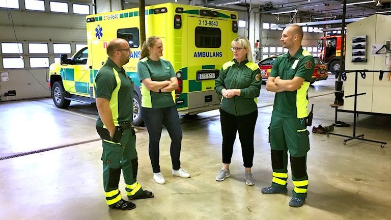 Fyra personer, personal från ambulans, står i ett garage med ambulanser i bakgrunden. Klädda i gröna och gula arbetskläder