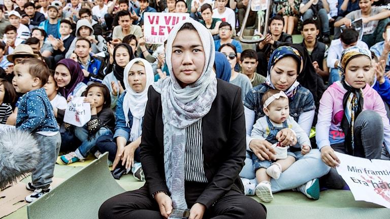 Afghansk kvinna framför en sittande folksamling