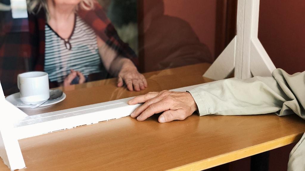 En äldre man som håller sin hand framför en äldre kvinna med ett plexiglas emellan.