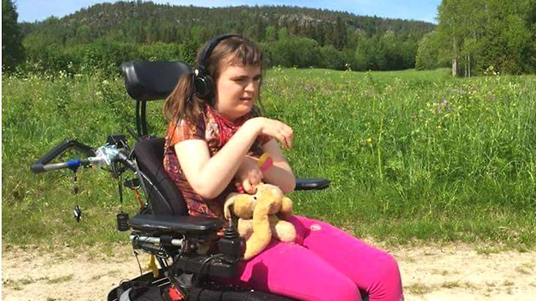 Felicia Henningsson kramar sin nalle och har rosa hörlurar på öronen.