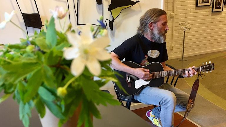 En bukett vitsippor i förgrunden, Larsa Eriksson spelar gitarr och sjunger i bakgrunden. Foto: Karin Lönnå/Sveriges Radio