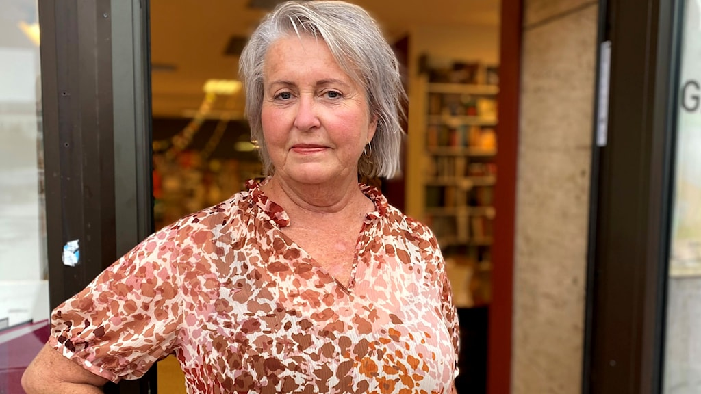 Kvinna står i dörröppningen till bokhandel.
