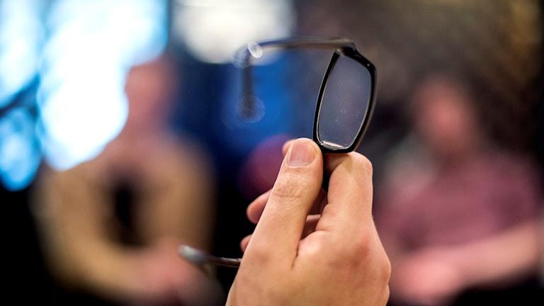 Närbild på en hand som håller i ett par glasögon. Foto: Pontus Lundahl/TT