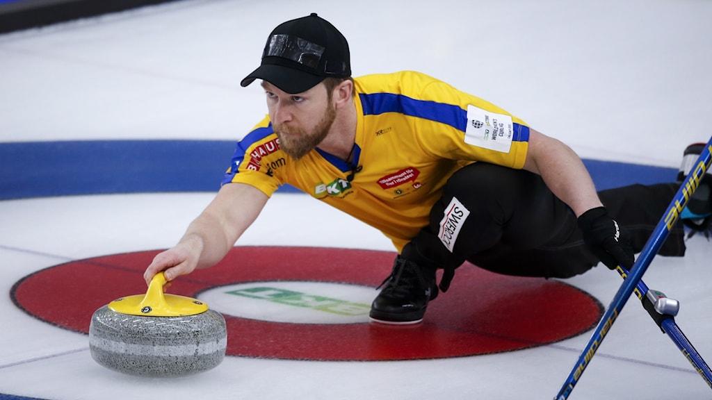 Manlig curlingspelare håller i en curlingsten på isen