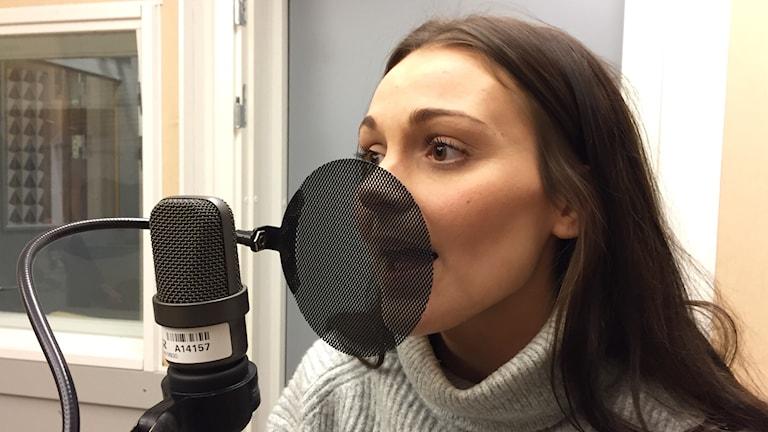 Maria Sandin sjunger i en mikrofon. Foto: Karin Lönnå/Sveriges Radio