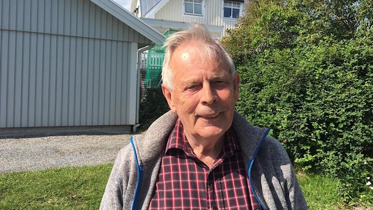 Johnny Löfstrand framför ett hus och en buske.