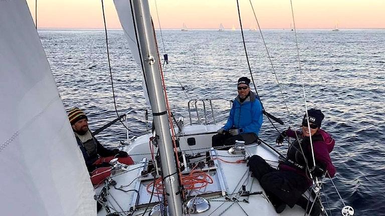 Team Skumpan med Pontus Jansson, Kristoffer Harmark och Anna Cedervall i segelbåten medan solen är på väg ner i horisonten. Foto: Team Skumpan