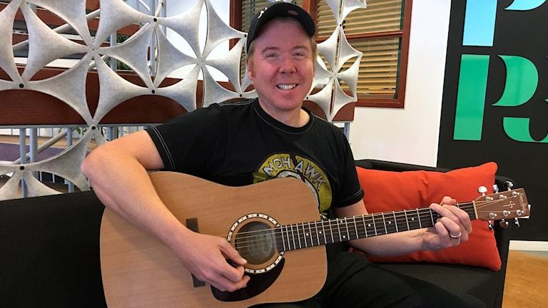 Magnus Engqvist sitter i soffa i radiohuset med sin gitarr. Foto: Ann-Charlotte Carlsson/Sveriges Radio