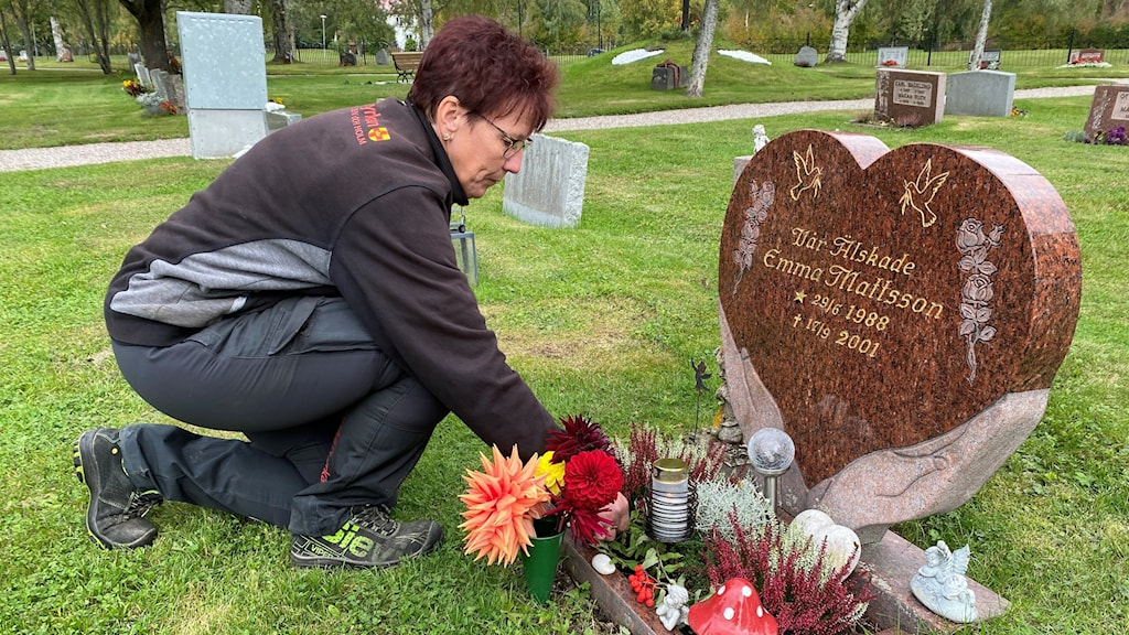 Kvinna som tänder ett ljus på en grav