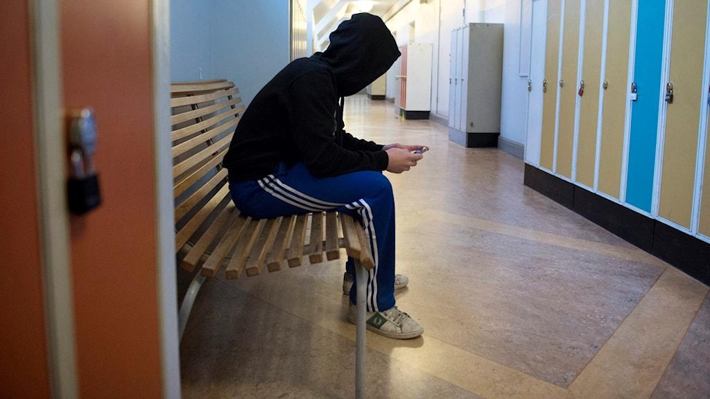 En elev i huvtröja sitter på en bänk i en korridor. Foto: Jessica Gow/TT