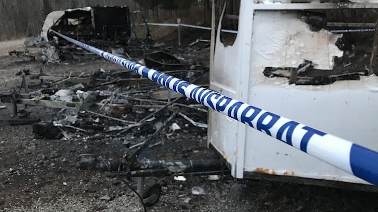 Utbrända husvagnar bakom polisens avspärrningsband. Foto: Anton Kårén/Sveriges Radio
