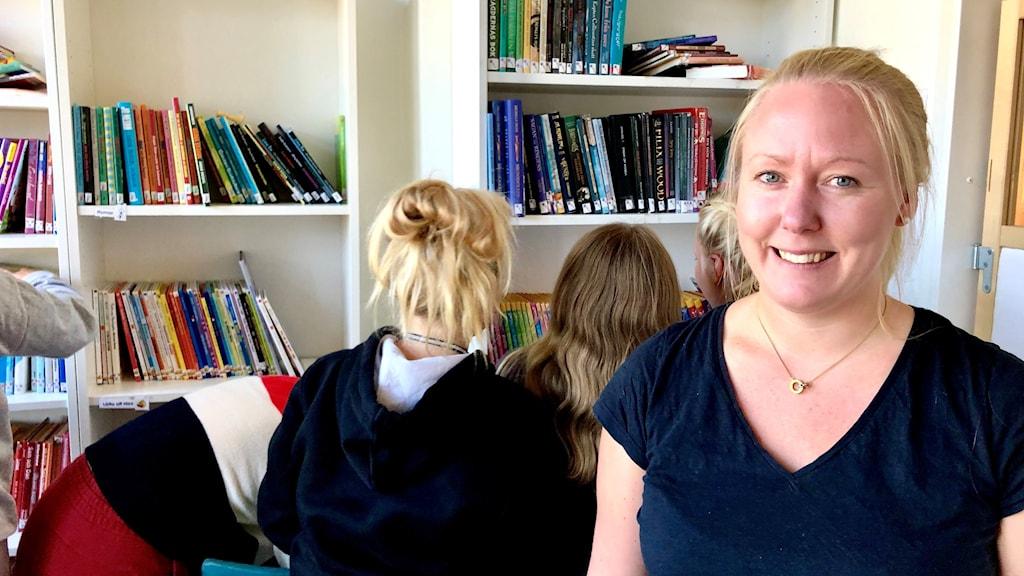 Caroline Sundström framför en bokhylla där massa barn rotar efter böcker.