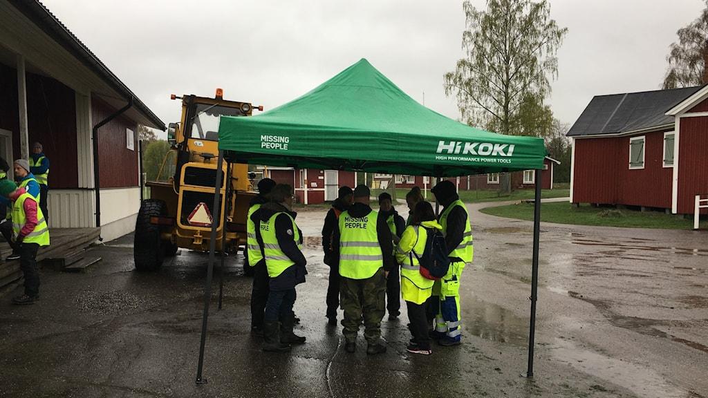 Under ett provisoriskt tält tar ett tiotal medlemmar av Missing People skydd från regnet, alla iförda gula västar. De står i en ring och ser ut att diskutera något.