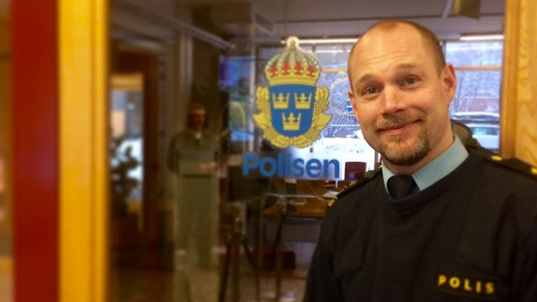 Andreas Zehlander står i entrén till Polishuset i Sundsvall. Bakom honom är en glasdörr med polisemblemet på. Andreas är snaggad med kort, välansad ansiktsbehåring. Han är klädd i tjock marinblå poliströja. Under den syns kragen till en ljusblå polisskjorta samt en mörkt marinblå slips. Han ler in i kameran och ser glad ut. Foto: Alexander Arvidsson/Sveriges Radio