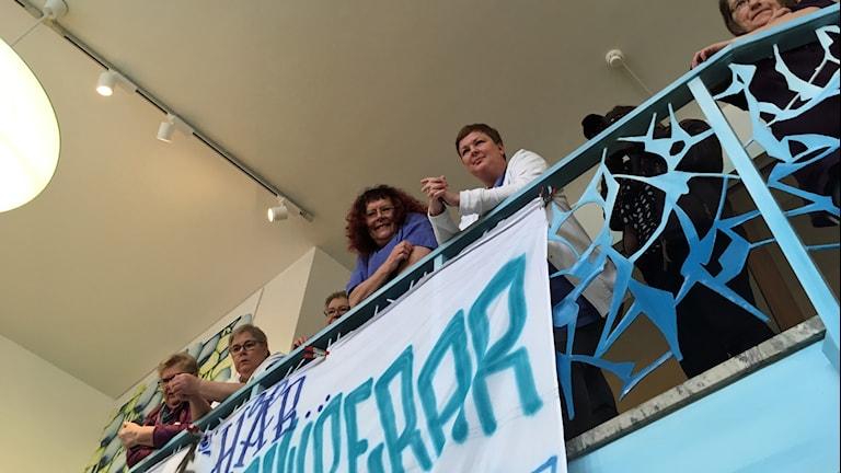 Åhörare som står högst upp i trappan och lyssnar på Lööf.