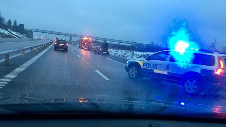 En polisbil med blåljus markerar en singelolycka på E4 söder om Sundsvall. Foto: Lotte Nord/Sveriges Radio