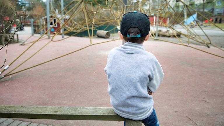 En pojke sitter ensam i en lekpark med ryggen mot kameran. Foto: Jessica Gow/TT
