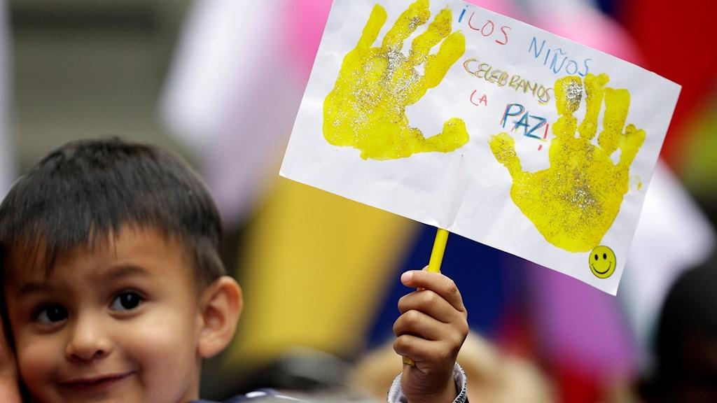 """Ett leende barn håller upp en teckning med texten """"Barnen firar freden""""."""