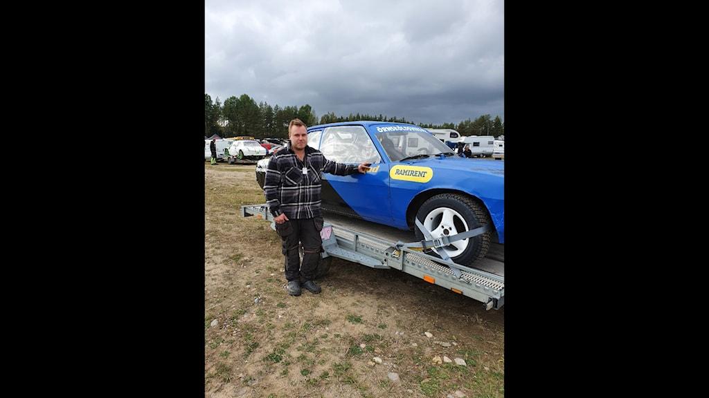 Pontus Häggblad framför sin blå folkracebil som är lastad på en släpvagn. Man får anta att bilden är tagen före ett race, för bilen är blänkande ren.