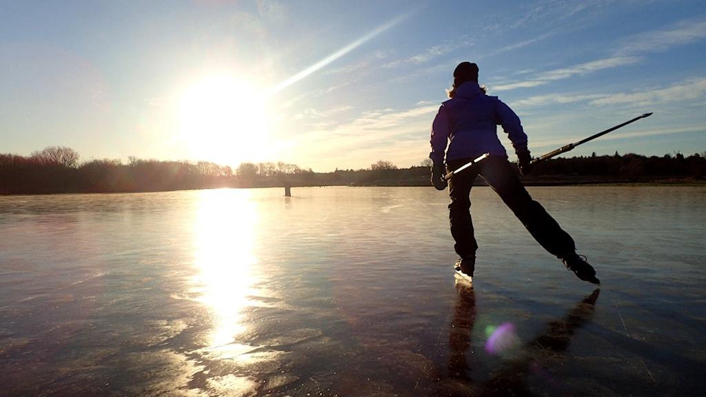 Person åker skridskor på en sjö under vintersolen.