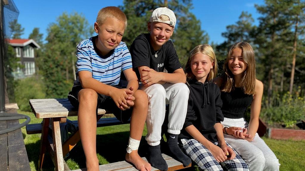 Två killar och två tjejer som sitter ute på en bänk.