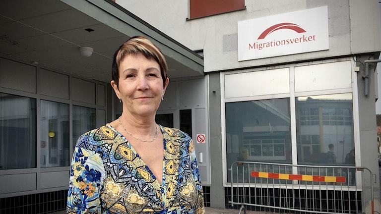 Kvinna står på trottoaren utanför Migrationsverket i Kramfors, Migrationsverkets logga och skylt i bakgrunden.