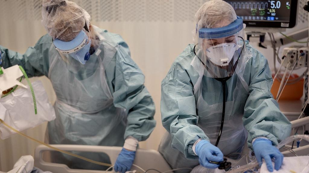 Intensivvårdsavdelningen på ett sjukhus, två personer jobbar med en patient.