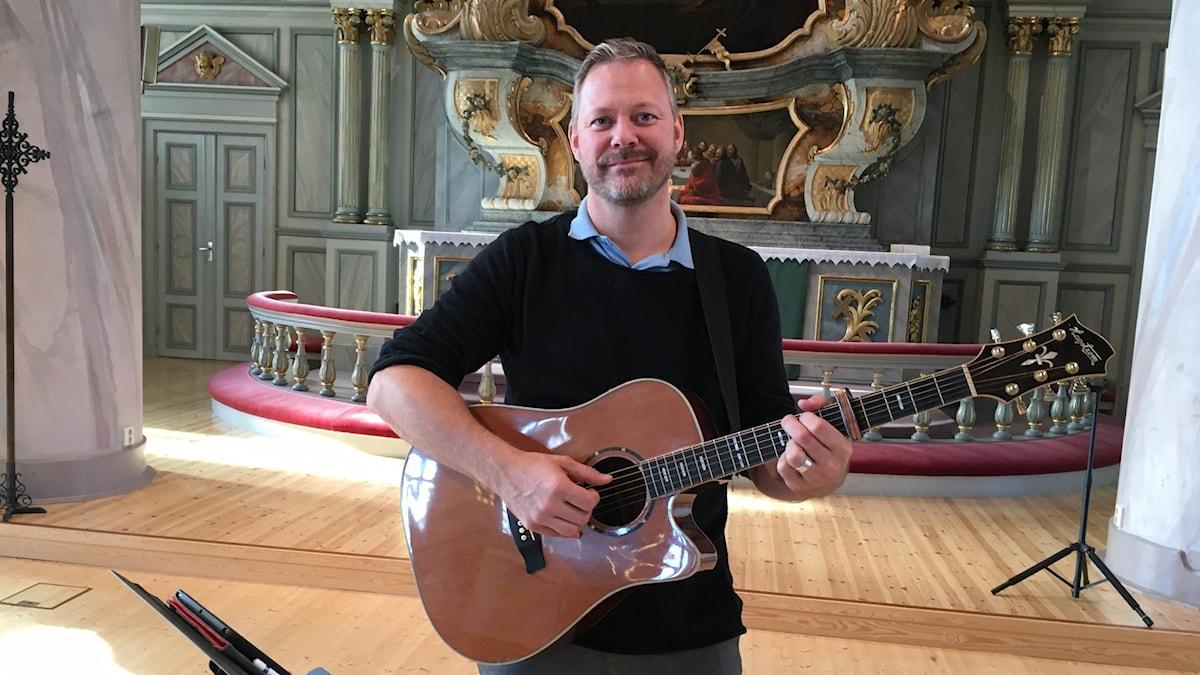 Niclas Lundin med en gitarr i kyrkan i Själevad.
