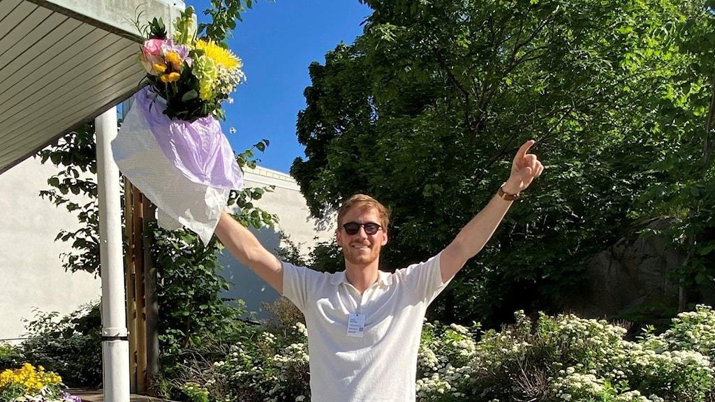 Vinnaren av P4 Nästa 2021 Joakim Gissberg står utanför radiohuset i Stockholm och sträcker armarna i skyn. I sin högra hand håller han en blombukett. Foto: August Svärdström.