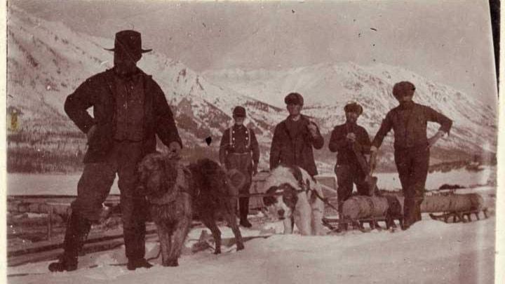 En svart-vit Fem män uppställda vid ett hundspann med snötäckta berg i bakgrunden.
