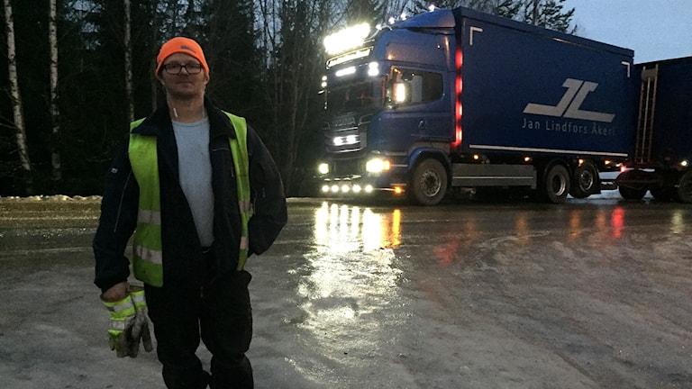 Chauffören Lars-Johan Högdahl på isen framför sin flisbil som inte tar sig vidare vid Sörfors på väg 548.