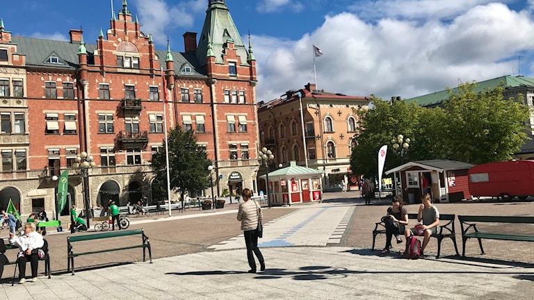 Några få männikor sitter på bänkar eller flanerar på Stora torget i Sundsvall.