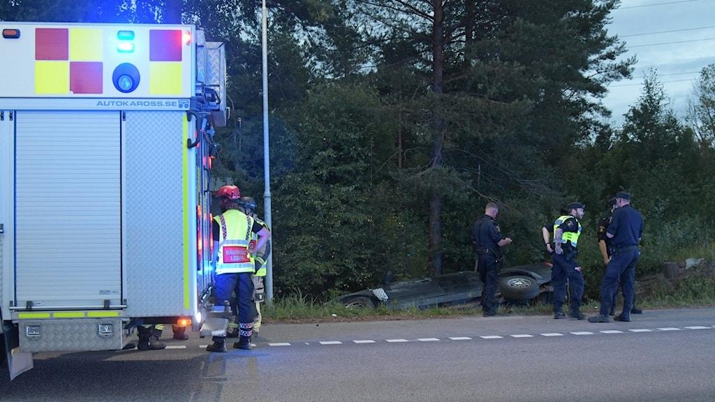 En del av en brandbil med blåljus på syns till vänster, bakom ligger en bil i ett dike och bredvid står några poliser.