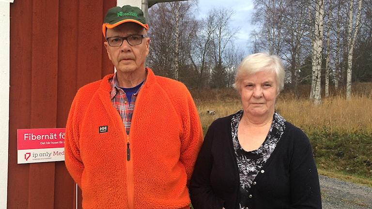 en äldre man och kvinna framför skylt från IP only