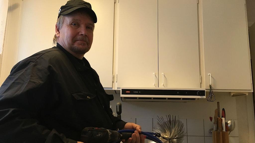 Ulf artursson är sotare och han står framför en köksfläkt.