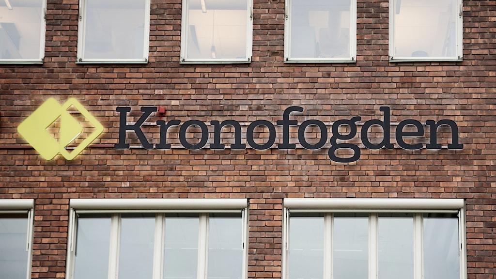 Kronofogdens logotyp på en tegelfasad. Foto: Vilhelm Stokstad/TT