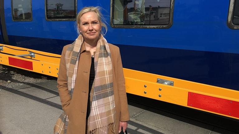 Anna Johansson, infrastrukturminister, poserar framför ett tåg.