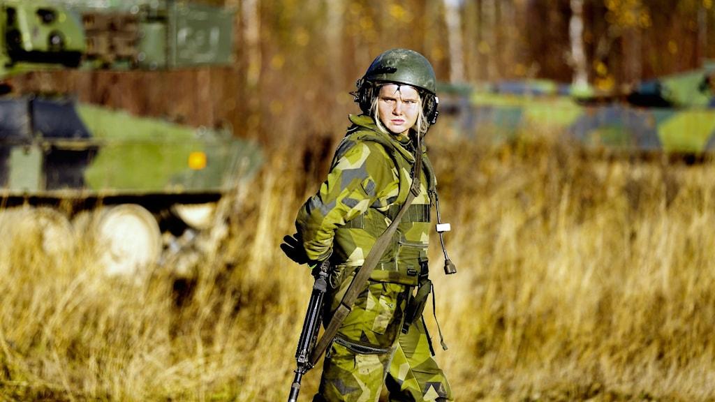 En bild på en soldat i skogen med pansarfordon i bakgrunden.