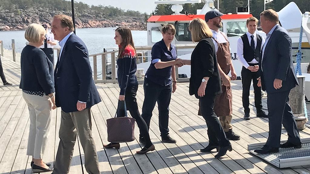 De nordiska ministrarna med Stefan Löfven i spetsen har anlänt till Ulvön och hälsas välkomna när det kliver av båten. Foto: Pether Öhlén/Sveriges Radio