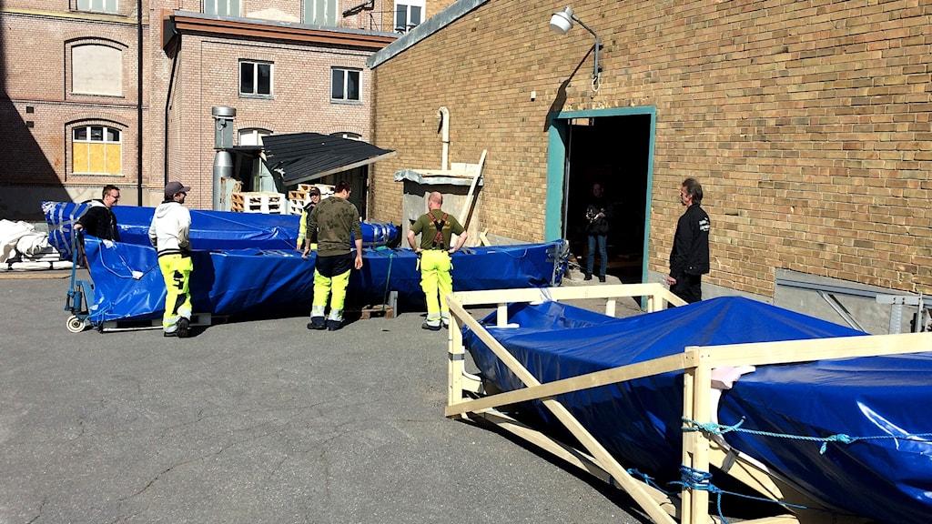 Fritidsbåtarna till nya museet i Härnösand anländer noggrannt insvepta i blå presenningar. Foto: Ulla Öhman/Sveriges Radio
