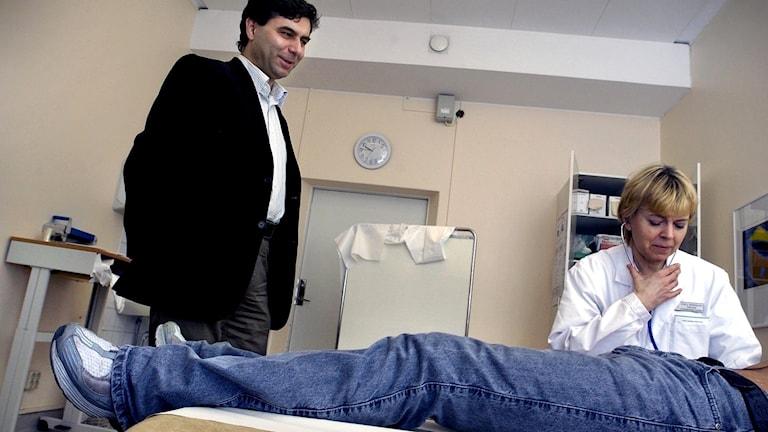 Ali Labriz (t.v.), tolkar åt en patient som ligger på en brits och blir undersökt av en läkare.