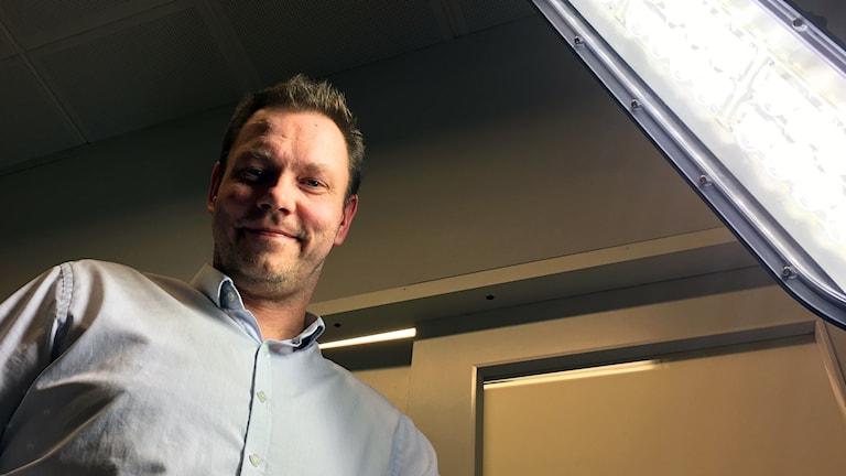 Rainer Rönnback står i skenet från en av de starka lampor som Jukolux tillverkar.