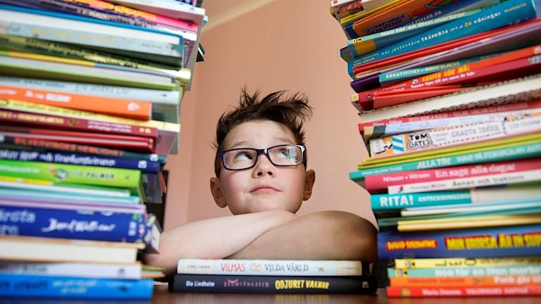Flicka tittar på höga staplar av barn- och ungdomsböcker.