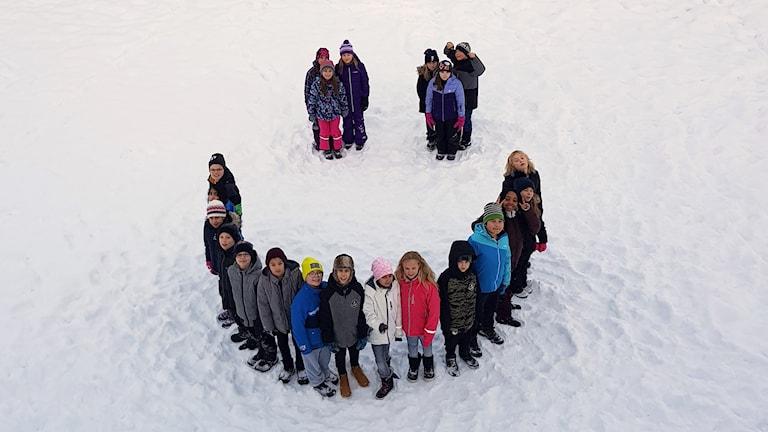 Klass 5A på Kristna skolan Oasen står som en smiley i snön på skolgården (två ögon och en glad mun). Foto: Minna Buijinck