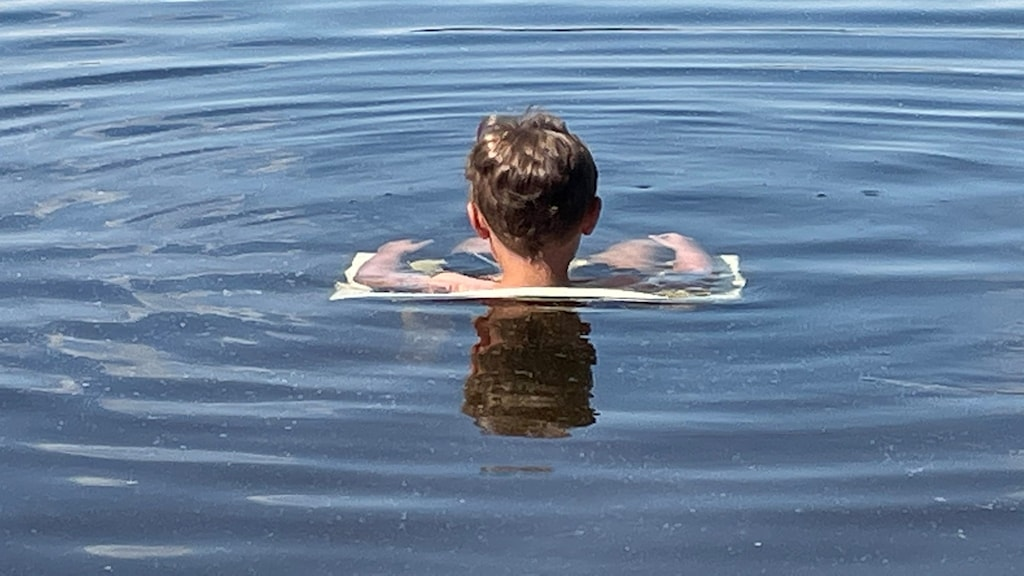 En liten pojke sitter på en plaststol ute i Långsjön. Bara huvudet sticker upp över ytan och man skymtar stolen och armstöden under vattenytan. Bilden är tagen bakifrån. Foto: Caj Lundqvist