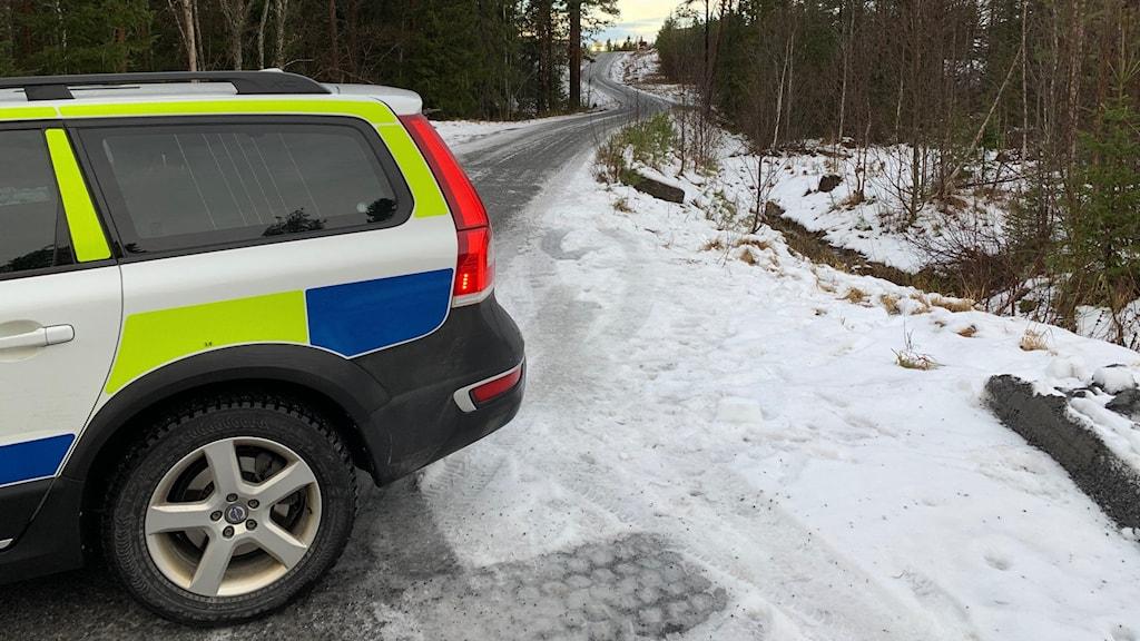 en polisbil på en snöig skogsbilväg