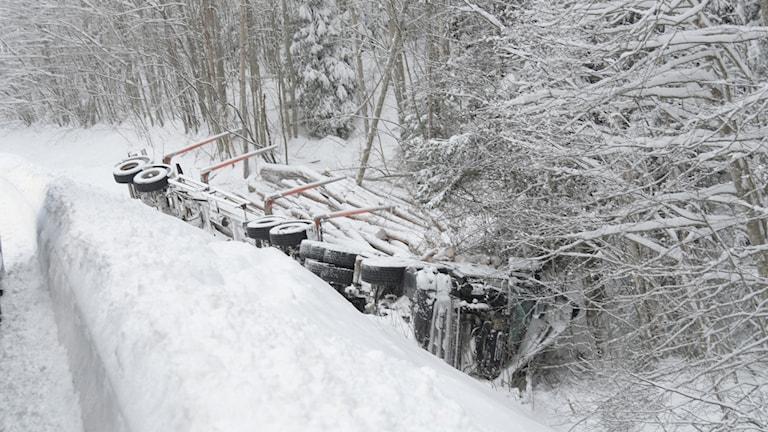 En timmerbil som ligger vält i ett djupt och snöfyllt dike.
